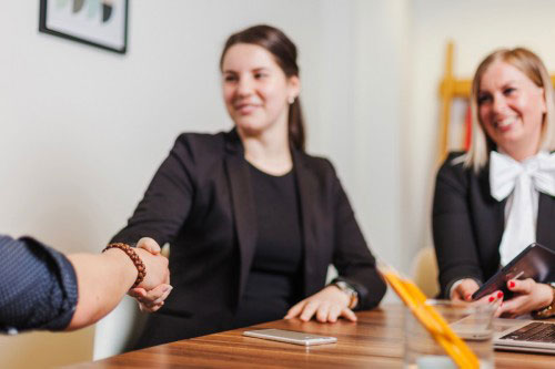Business women in an office shaking hands. Career article 'Emotional intelligence gives women an upper hand as negotiators' on Women@Work.