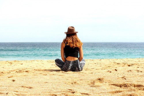 Woman chilling on a beach. Training article on Women@Work 'Ways to Improve Workplace Flexibility'